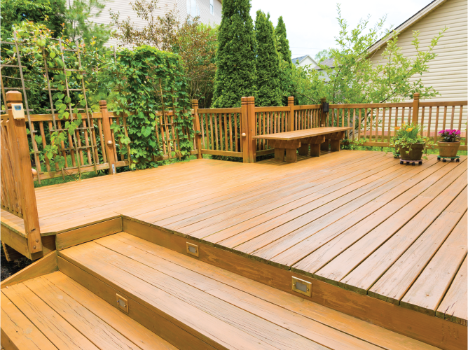 landscaped tiered wooden deck with gate and bench