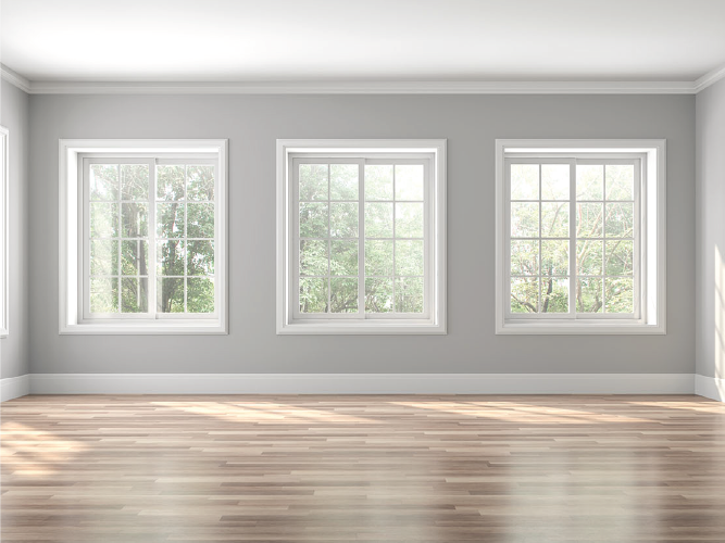 Sunny room with wood floors, grey walls and large framed windows